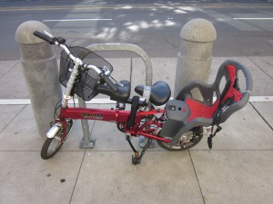 That's a rear child seat, a double front saddle, and a front cargo basket on a folding bike. Damn!