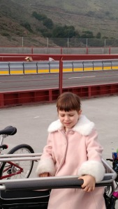 Little girl on a big bike, and an empty expanse where the cars usually go
